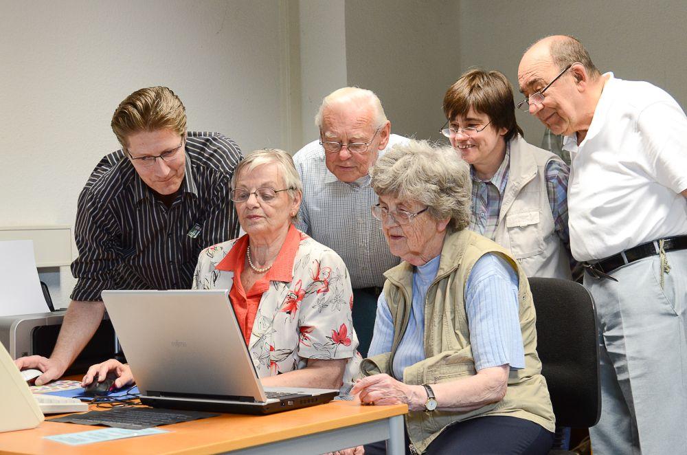 Eine Gruppe Senioren und ein Dozent betrachten an einem Computer