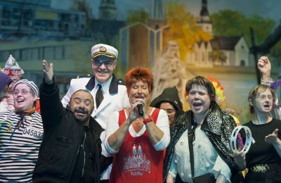 Marita Köllner mit Beschäftigten der SBK-Werkstätten auf der Bühne der Mülheimer Stadthalle