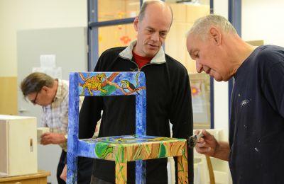 Ein Mitarbeiter der Pädagogischen Werkstatt im Gespräch mit einem Teilnehmer, der gerade einen Stuhl bemalt