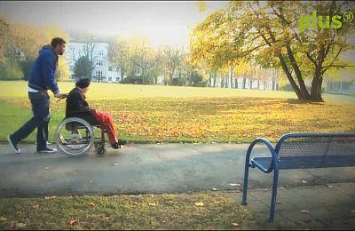 """Szene aus """"Mission Mittendrin"""": Steffen König schiebt eine SBK-Bewohnerin im Rollstuhl durch den Park in Riehl"""
