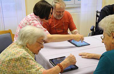 Bewohnerinnen und Bewohner des Seniorenzentrum Riehl sammeln zusammen mit einer Betreuerin erste Erfahrungen am Tablet-PC
