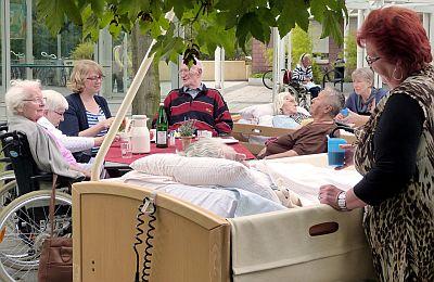 Bewohnerinnen und Bewohner mit Angehörigen und Mitarbeiterinnen der Sozialen Betreuung auf der Bettenterrasse