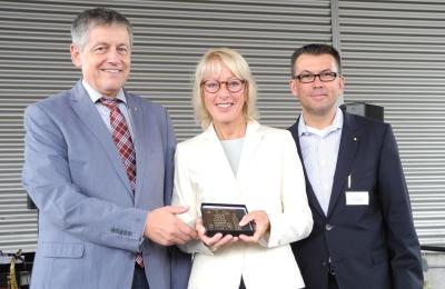 Bürgermeisterin Elfi Scho-Antwerpes überreicht SBK-Geschäftsführer Otto B. Ludorff (links) und Thomas Ebert, Leiter der SBK-Werkstätten, eine Plakette zum 25-jährigen Bestehen der Werkstatt Poll.