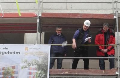 Polier Benedikt Weckbecker schmeißt nach geleistetem Richtspruch sein Glas zu Boden. Rechts Ossi Helling, Vorsitzender des SBK-Aufsichtsrates, links SBK-Geschäftsführer Otto B. Ludorff.