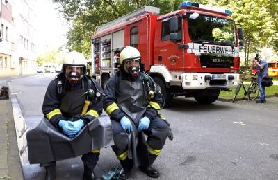 Zwei Feuerwehrleute sitzen im Schutzanzug vor einem Fahrzeug der Kölner Feuerwehr