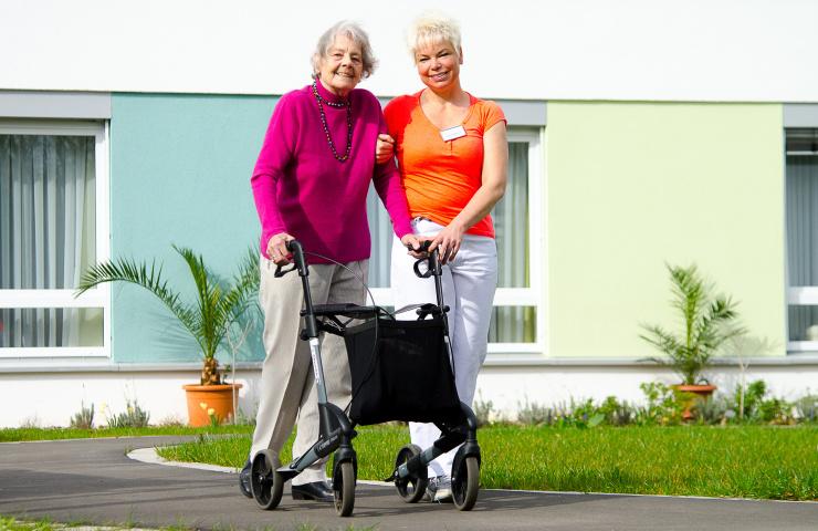 Bewohnerin und Mitarbeiterin im Garten eines neu erbauten Pflegeheims.