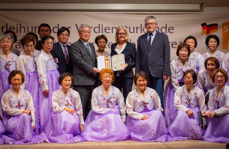 In der Mitte Generalkonsul Lee Dooyoung und SBK-Geschäftsführerin Gabriele Patzke mit der Verdiensturkunde