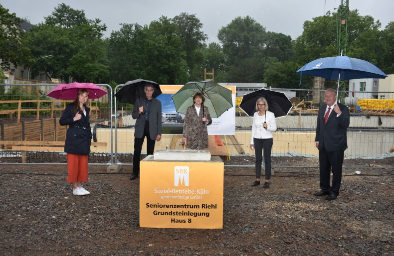 Gruppenbild nach Grundsteinlegung mit Abstand und Regenschirm (von links): Susanne Bokelmann, Ossi Helling, Henriette Reker, Gabriele Patzke und Thomas Brauckmann